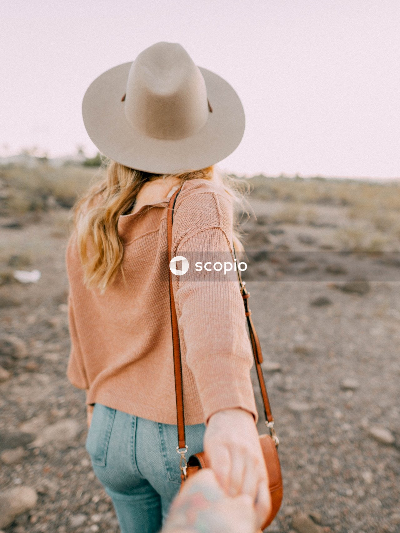 Woman in brown long sleeve shirt and blue denim jeans wearing white cowboy hat