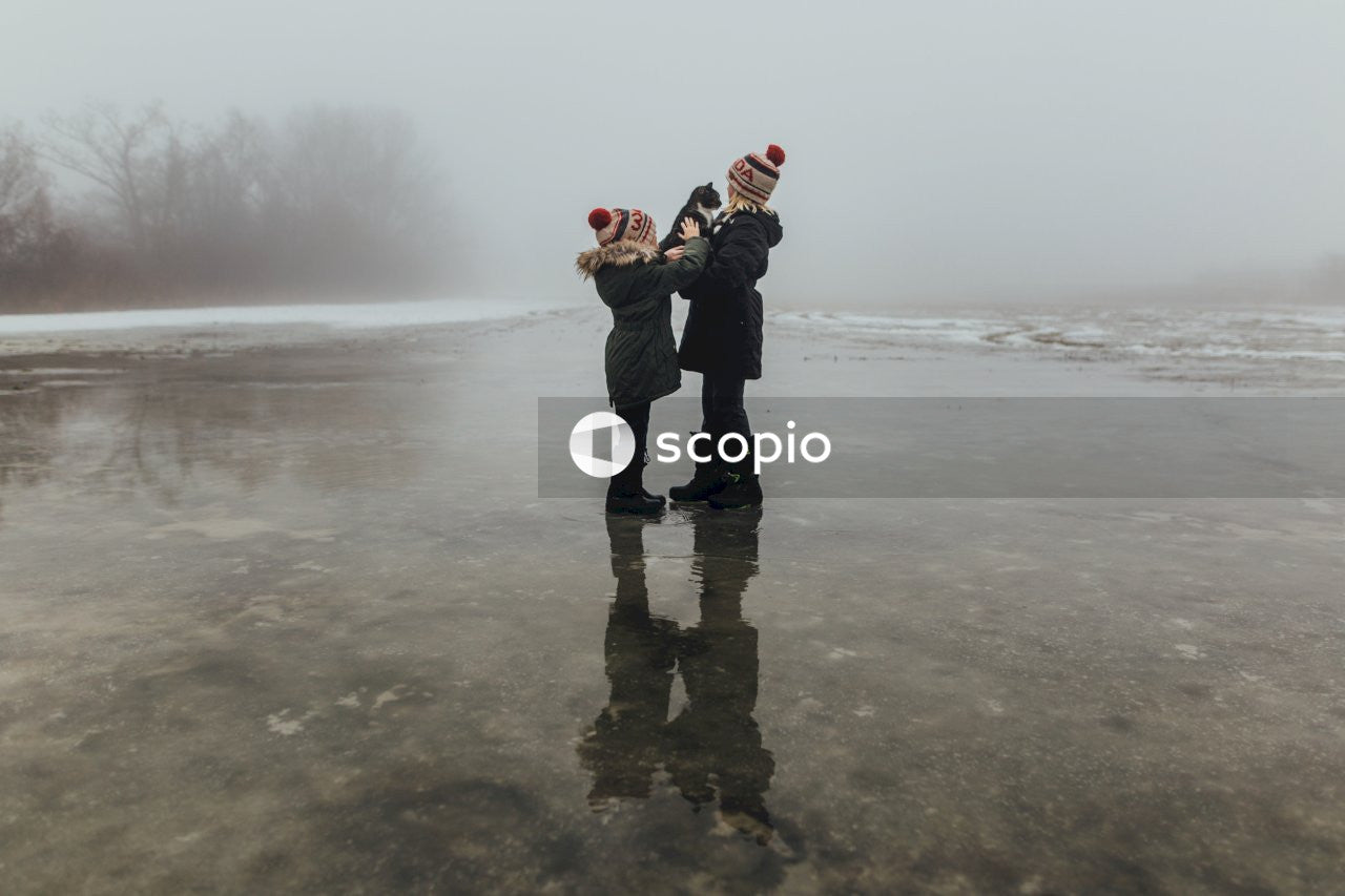 Two person standing on ice floor at daytime