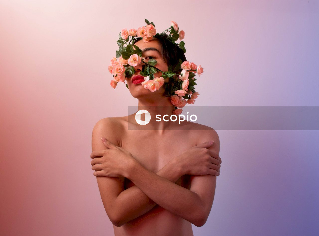 Topless woman with white and green flower on her head