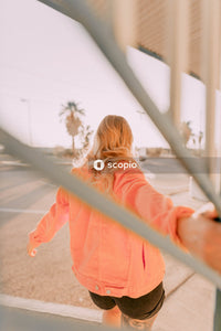 Girl in pink jacket standing on white bridge