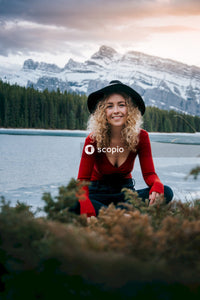 Woman in red long sleeve shirt and black hat sitting on brown grass field near lake