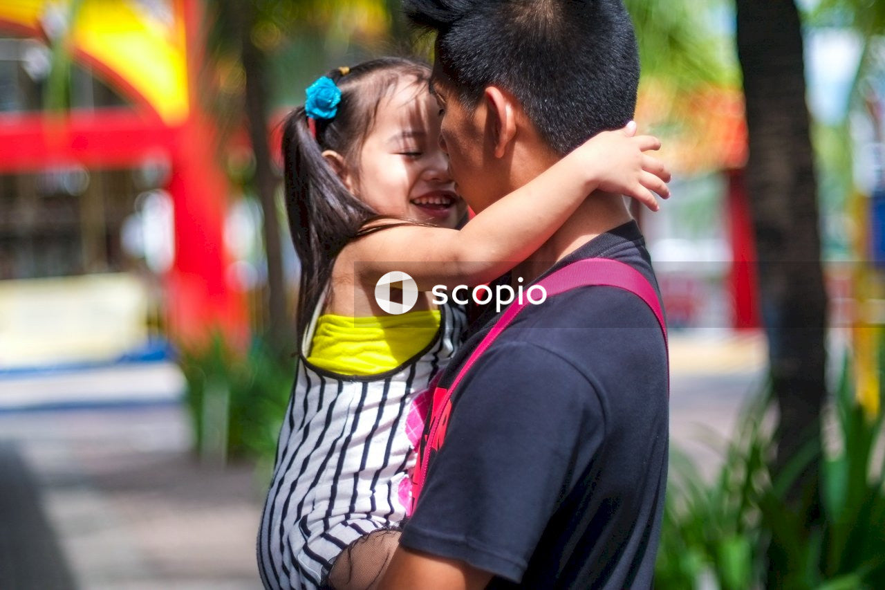 Selective focus photography of man carrying girl smiling