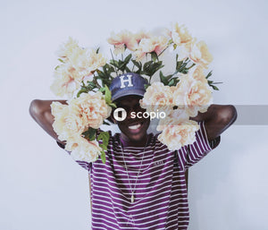 Portrait of man holding artificial flowers