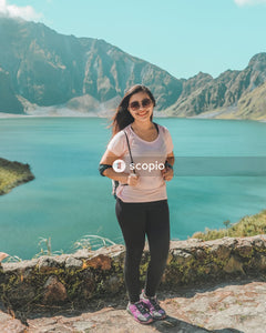 Woman in pink long sleeve shirt and black pants standing on rocky shore