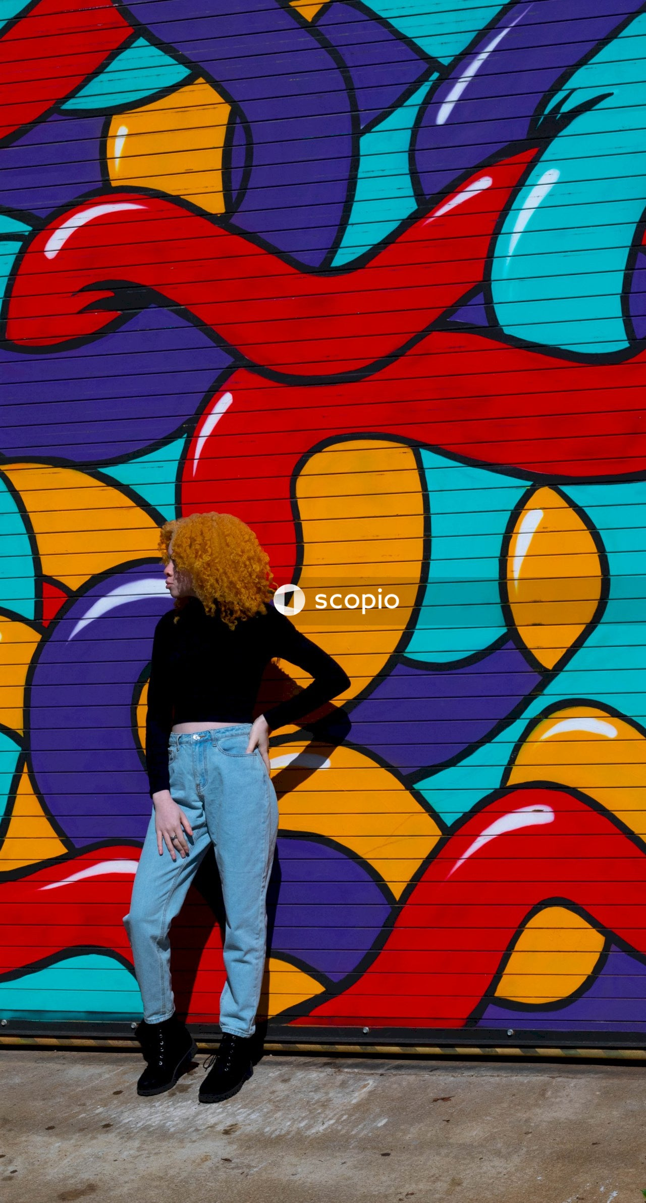Woman in black long-sleeved shirt and blue jeans standing beside graffiti wall