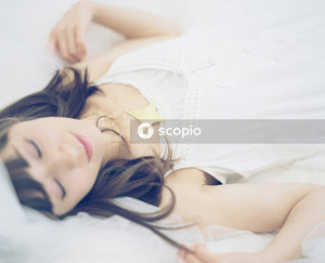 Woman in white sleeveless dress lying on bed