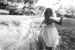 Grayscale photo of girl walking on grass
