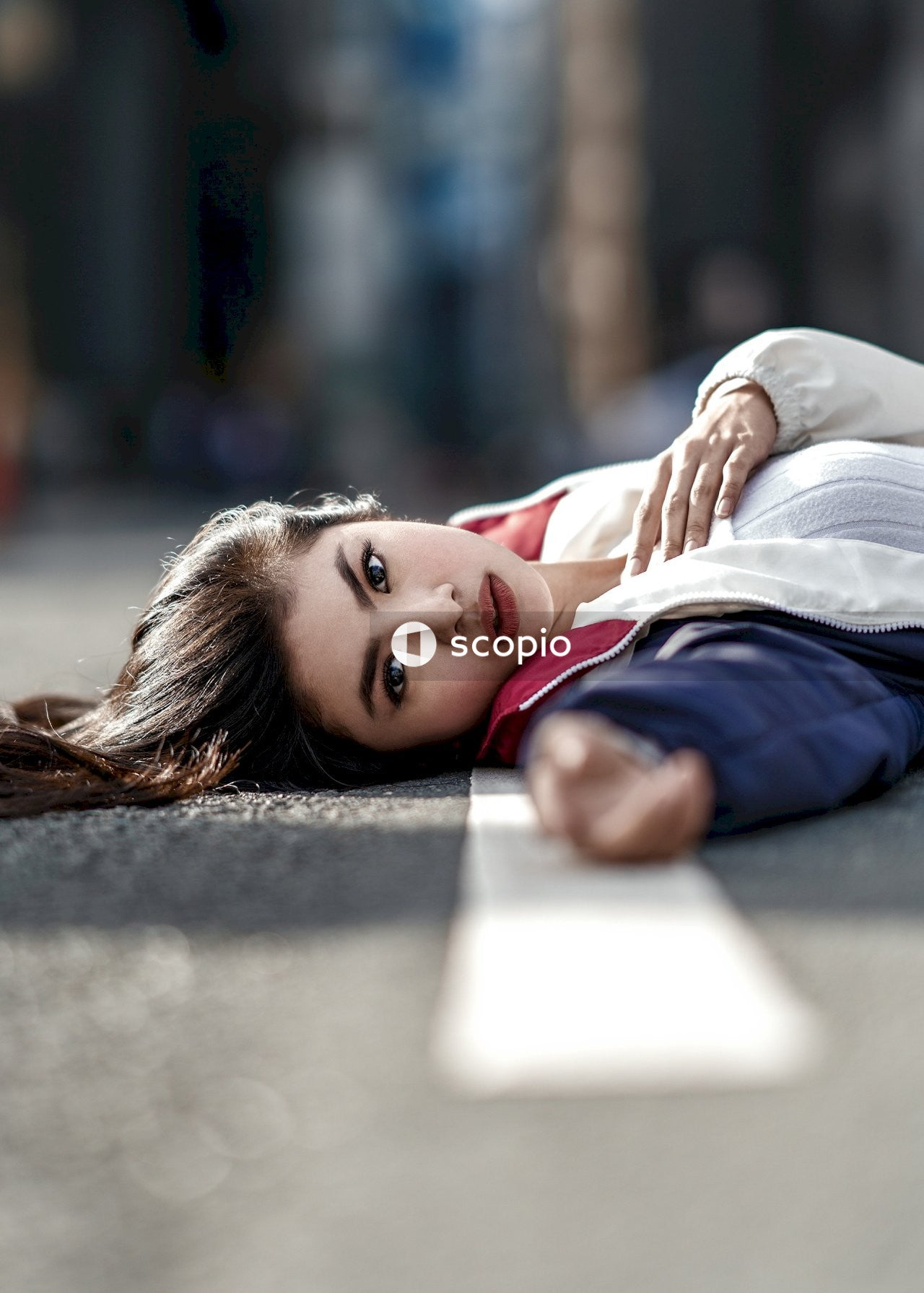 Woman in blue and red jacket lying on road