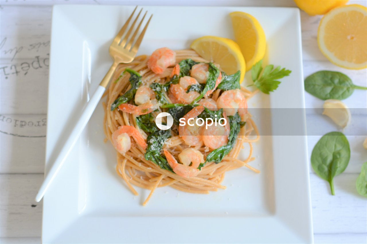 Pasta with green vegetable and sliced lemon on white ceramic plate