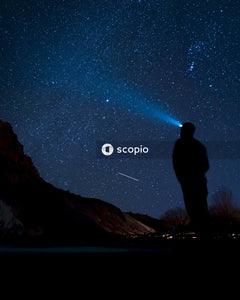 Man standing on rock formation under starry night