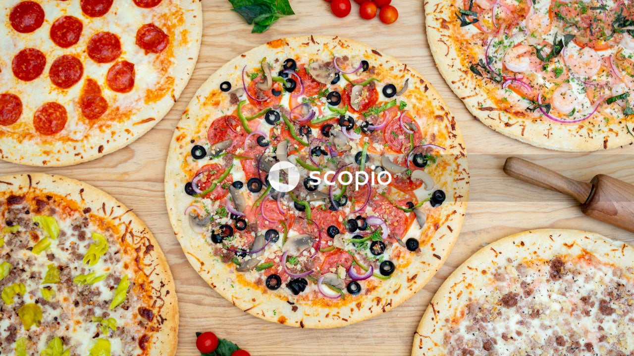 Pizza with cherry and green leaves on white ceramic plate