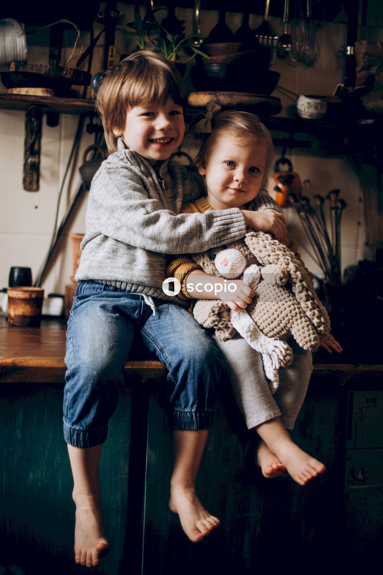 Little blond boy sitting on table hugging baby girl