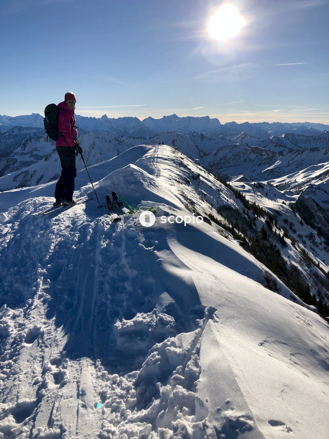 Person in red jacket and black pants standing on snow covered mountain