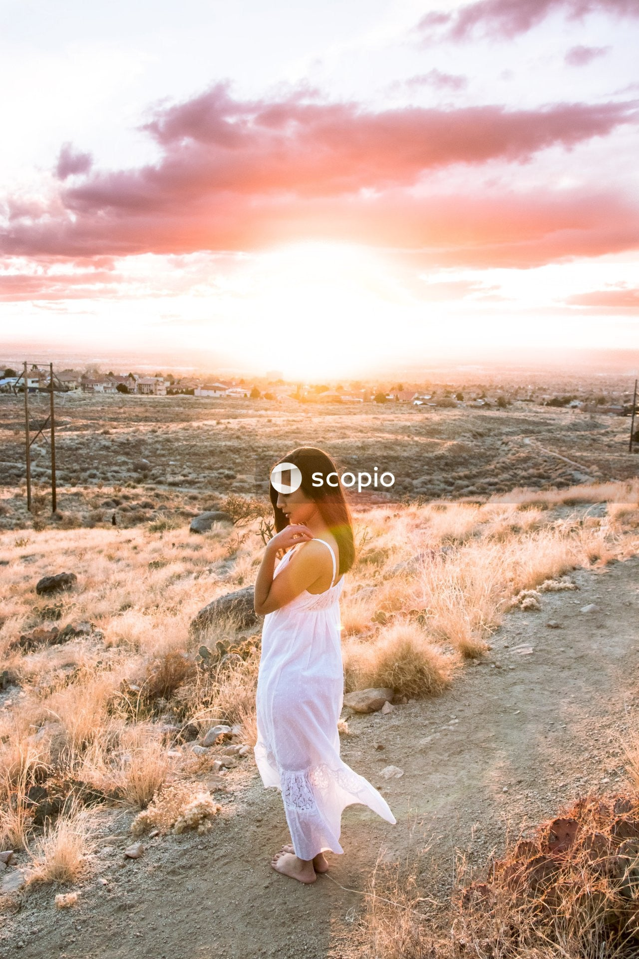 Woman in white tank top and white skirt standing on dirt road