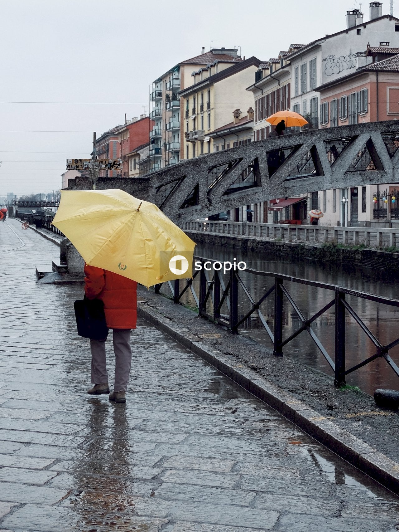 Woman in red coat holding yellow umbrella walking on sidewalk