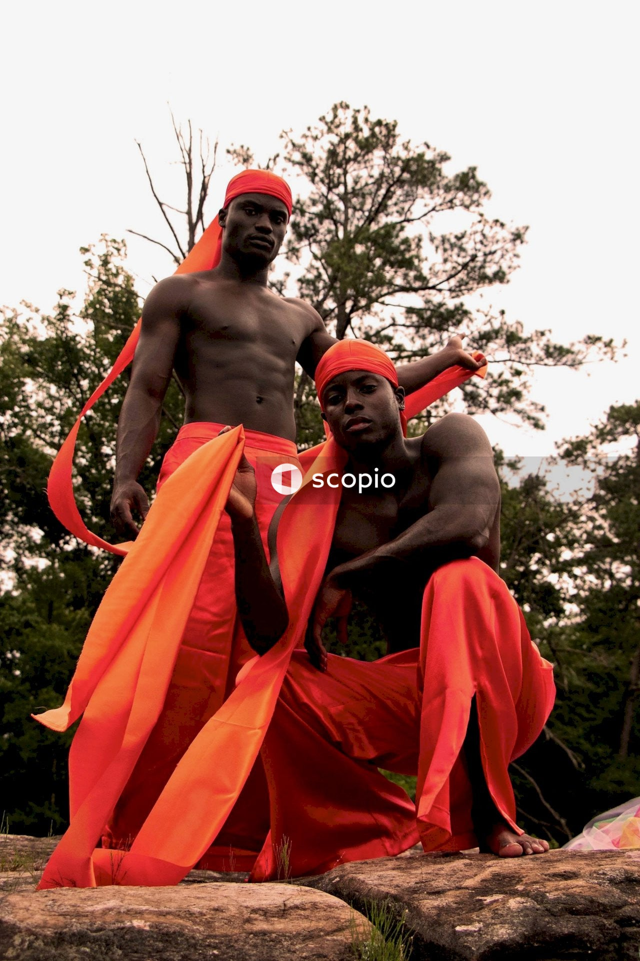 Two topless men in orange outfit standing on rock