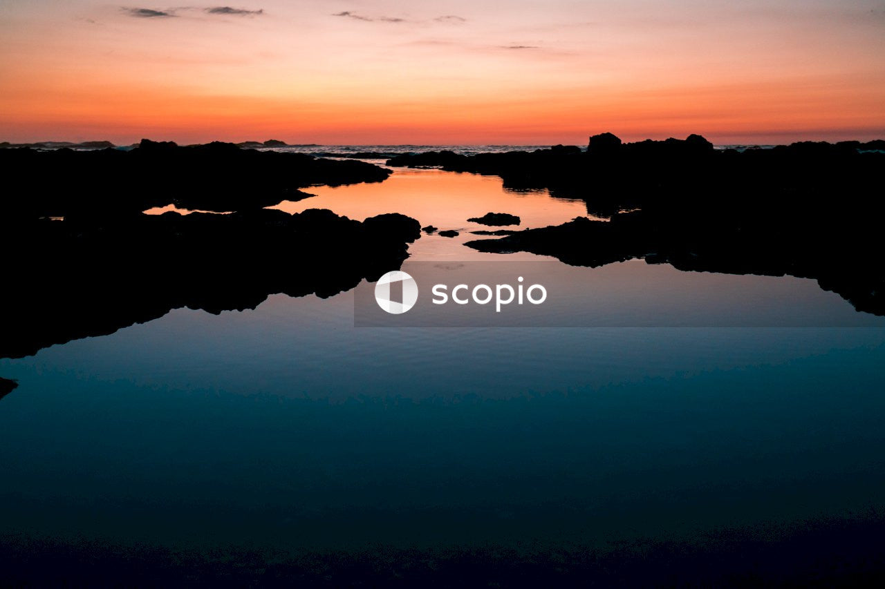 Silhouette of rocks on water during sunset