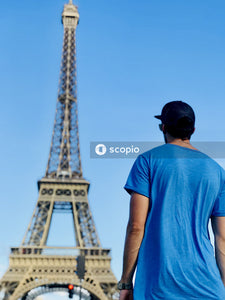 Man in blue crew neck t-shirt standing near eiffel tower