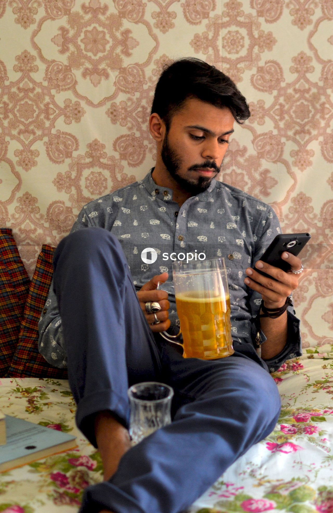 Man in gray and white floral button up shirt holding black smartphone
