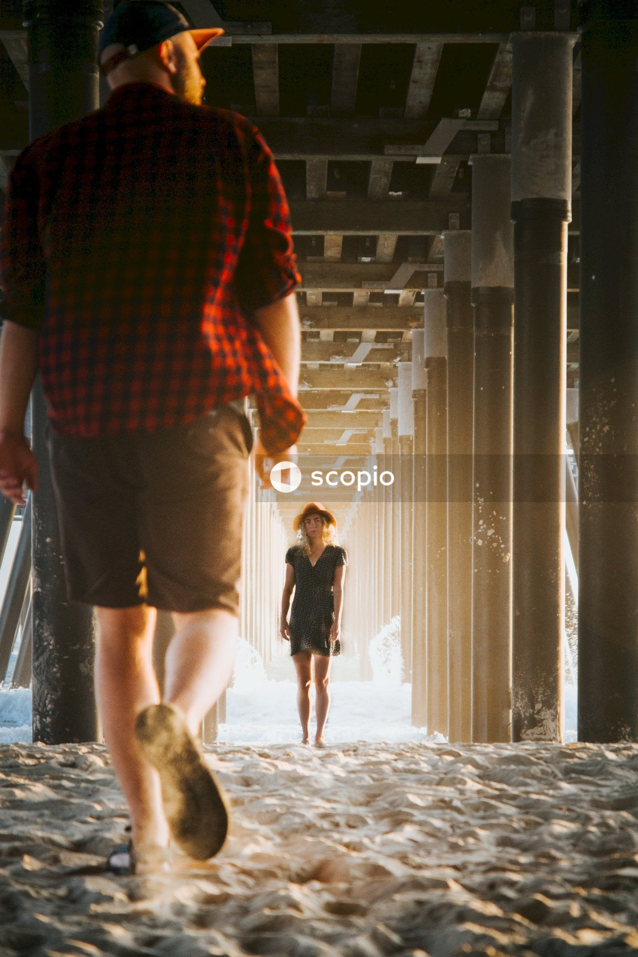 Man in red and black checkered shirt and brown shorts walking towards woman in black dress
