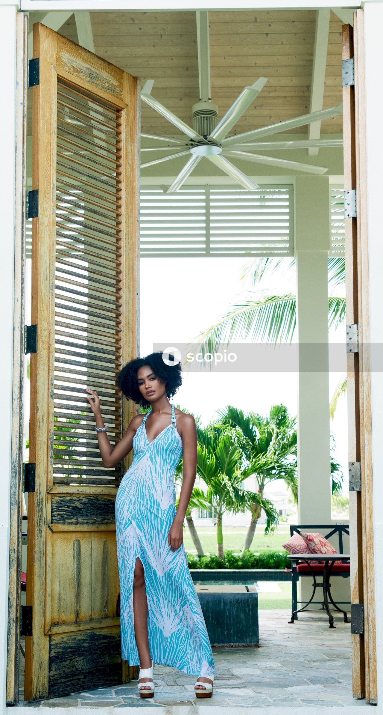 Woman in blue sleeveless dress standing near brown wooden door