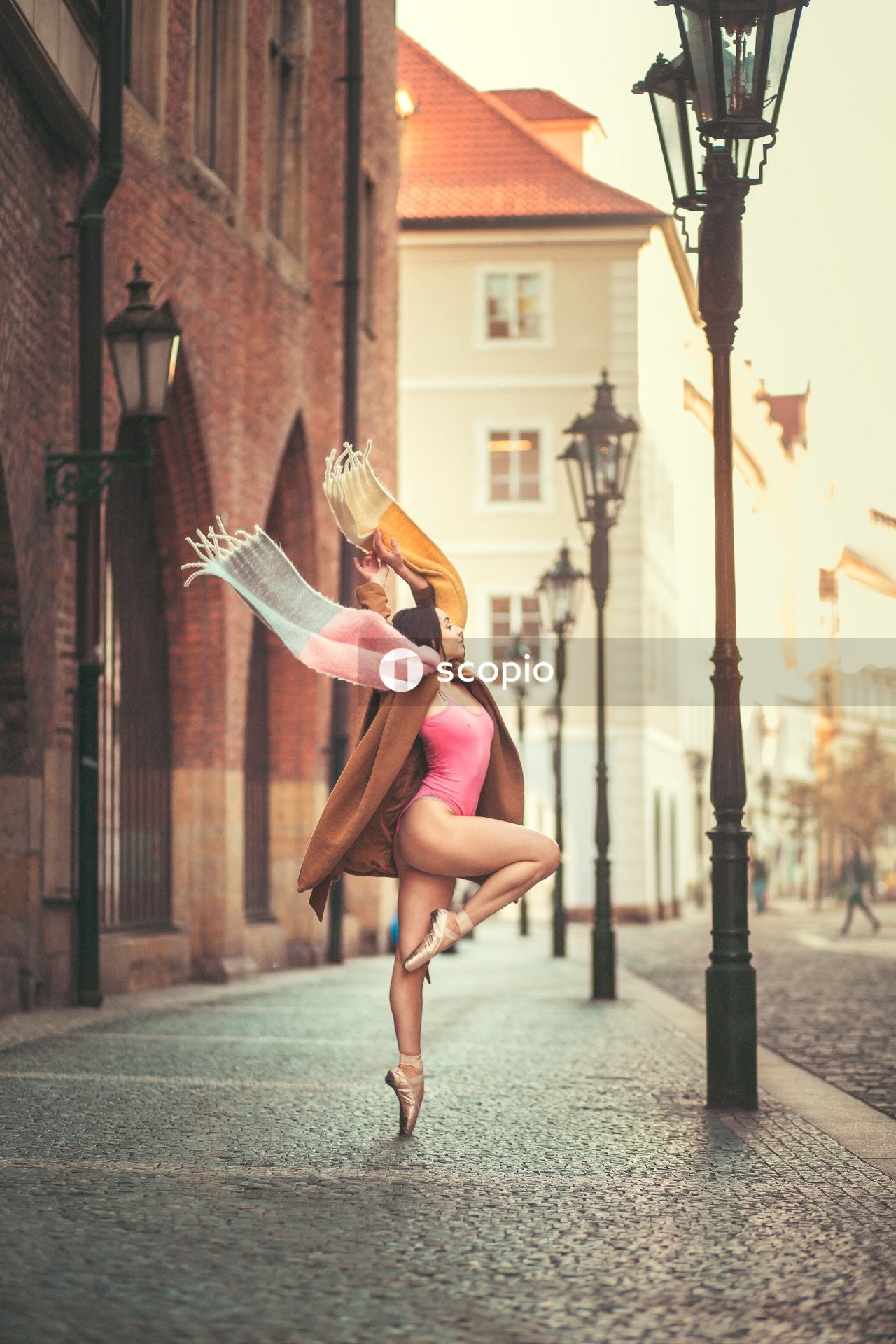Ballerina in pointe position near street lamp wearing brown coat
