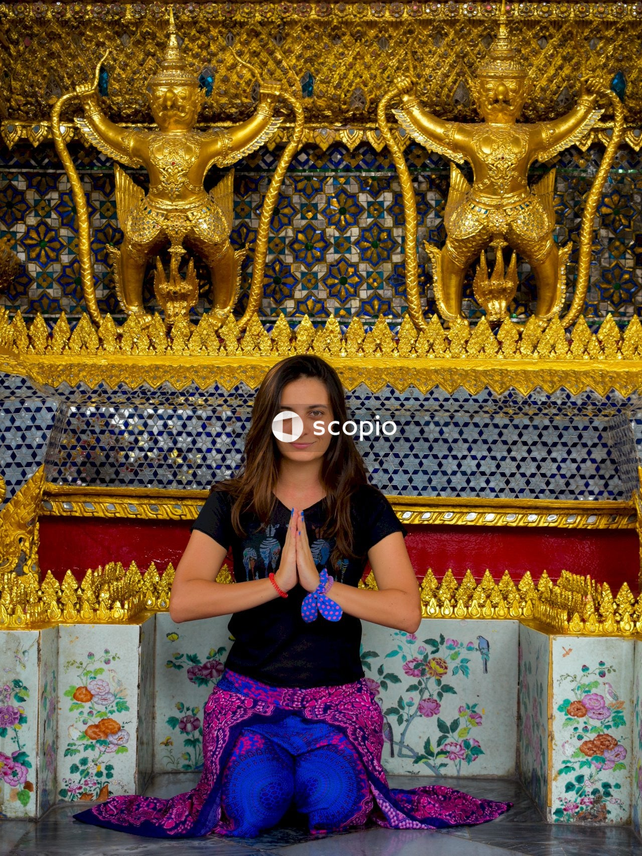 Woman in blue shirt and purple skirt standing near gold and red dragon wall