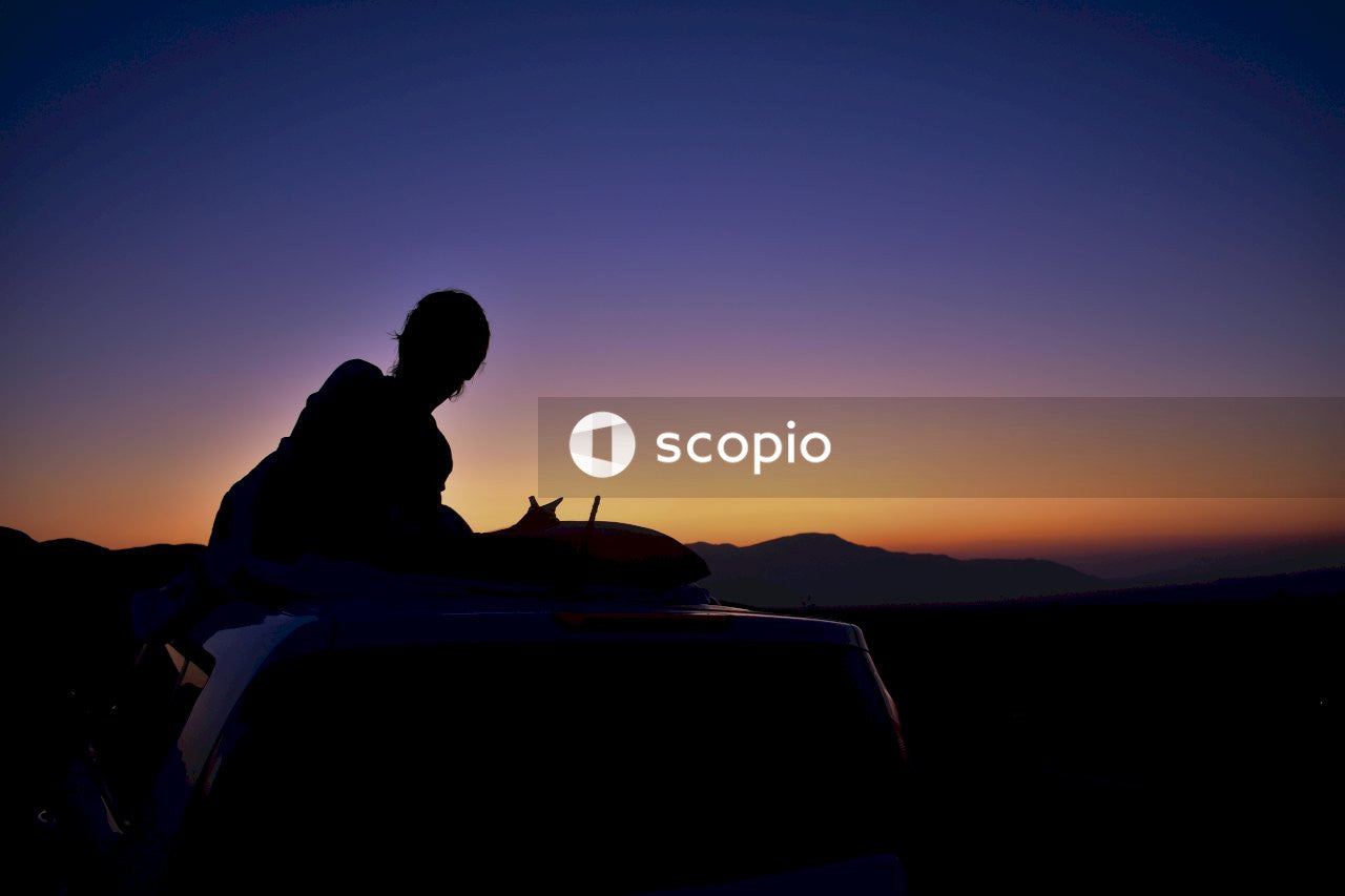 Silhouette of man sitting on car during sunset