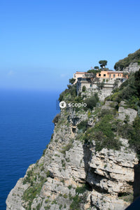White and brown concrete building on cliff by the sea under blue sky