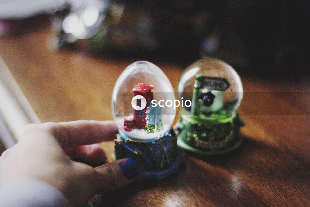 Person holding white and green ceramic snow globe