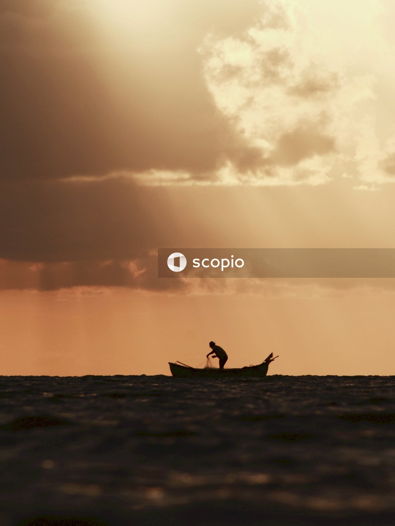 Silhouette of man on boat fishing with a net during sunset