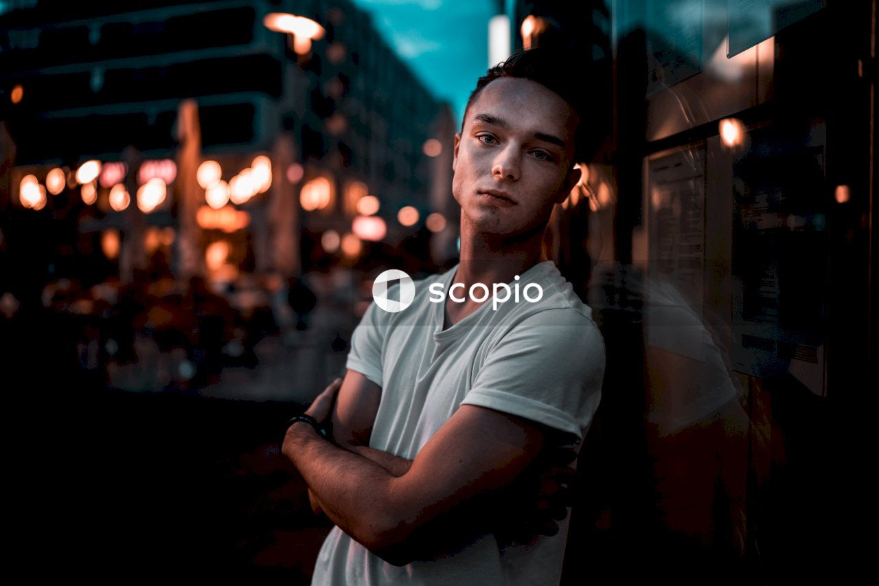 Man in white crew neck t-shirt standing near glass wall during night time