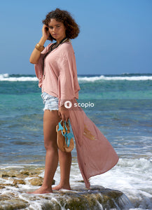 Woman in white long sleeve shirt and blue denim shorts standing on beach shore