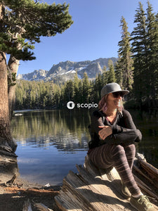 Woman in black long sleeve shirt and black pants sitting on brown tree log