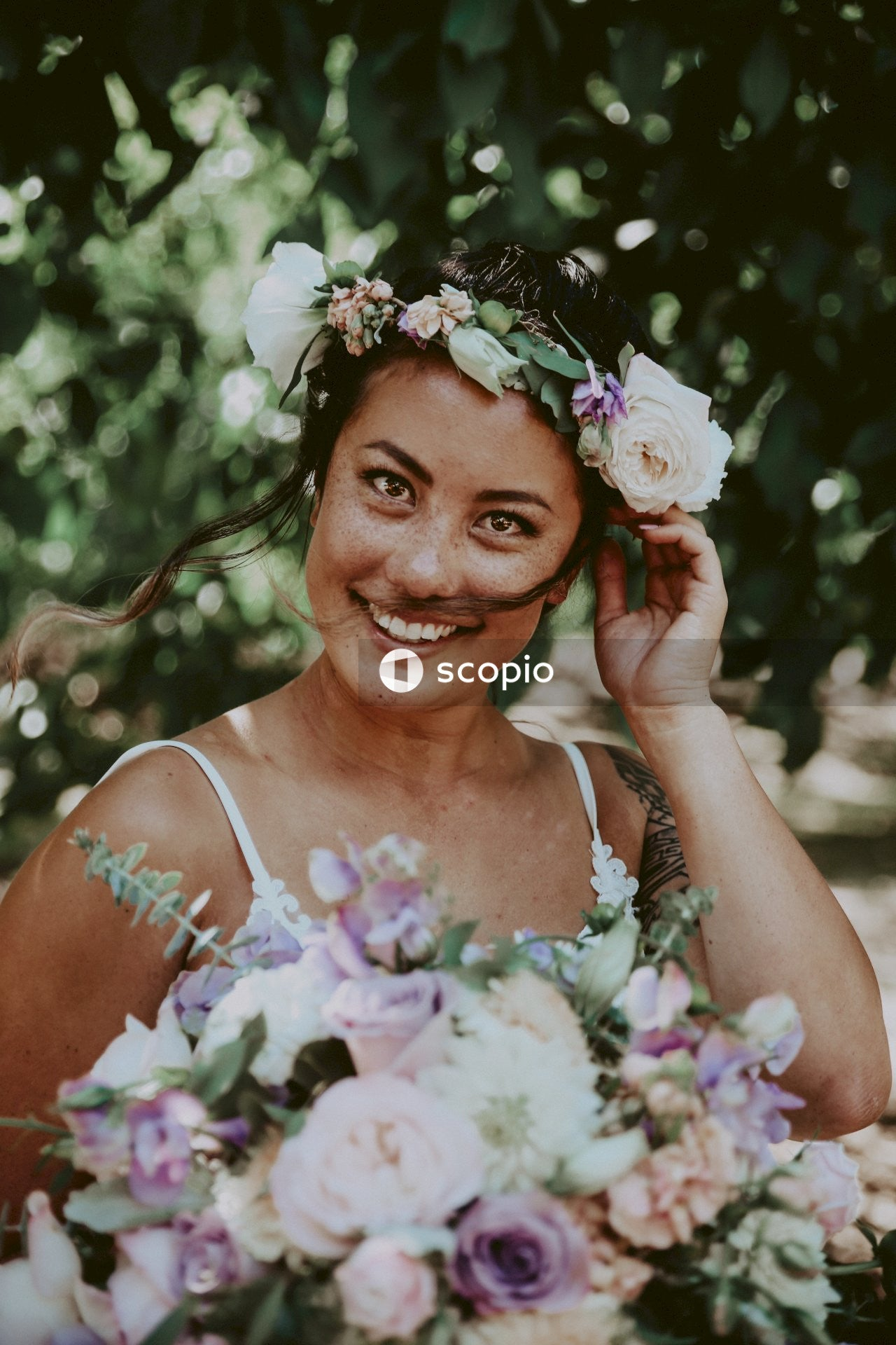 Smiling woman in white tank top holding bouquet of flowers