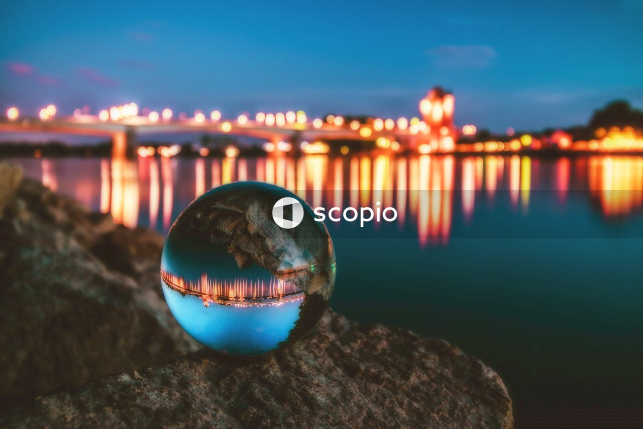 Clear glass ball on black rock near body of water during night time