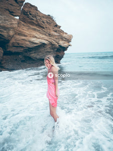 Woman in teal spaghetti strap dress standing on brown rock formation near body of water