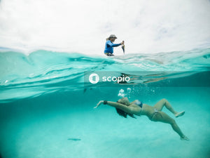 Underwater shot of woman swimming while a man standing on land