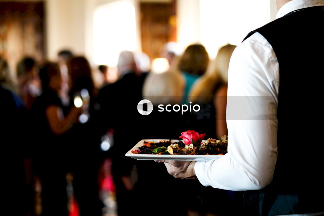 Man in white dress shirt holding tray with food