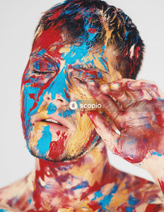 Portrait of man with colorful paint on his face touching his eye with his hand