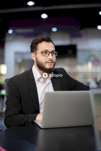 Man in a suit working on a laptop