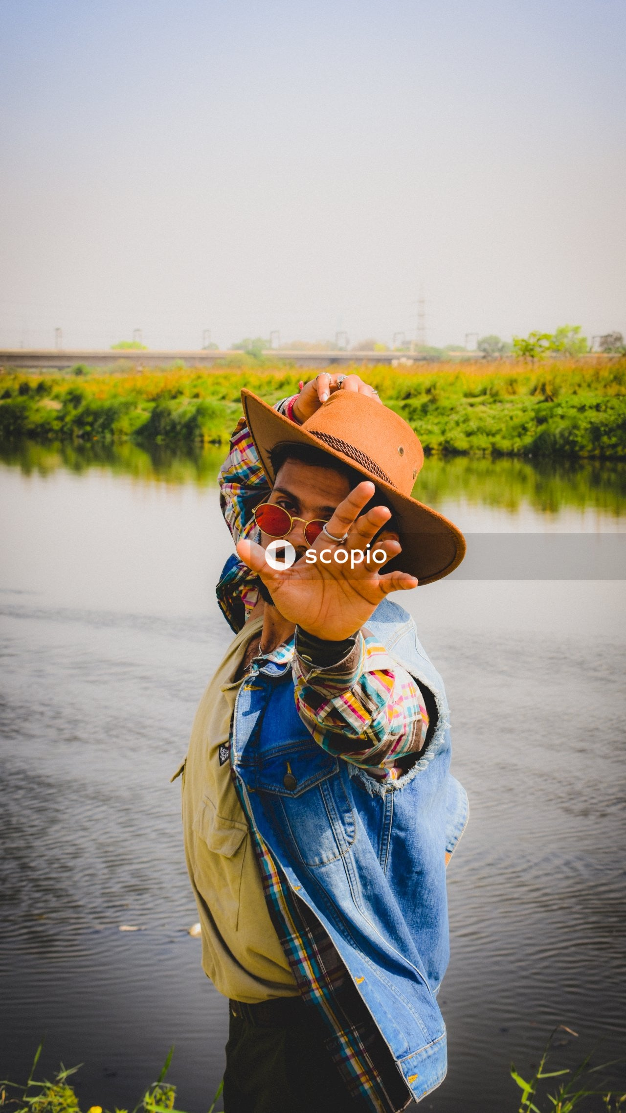 Woman in blue denim jacket wearing brown hat standing near body of water