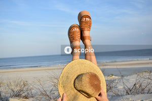 Person wearing brown leather sandals and brown sun hat standing on beach