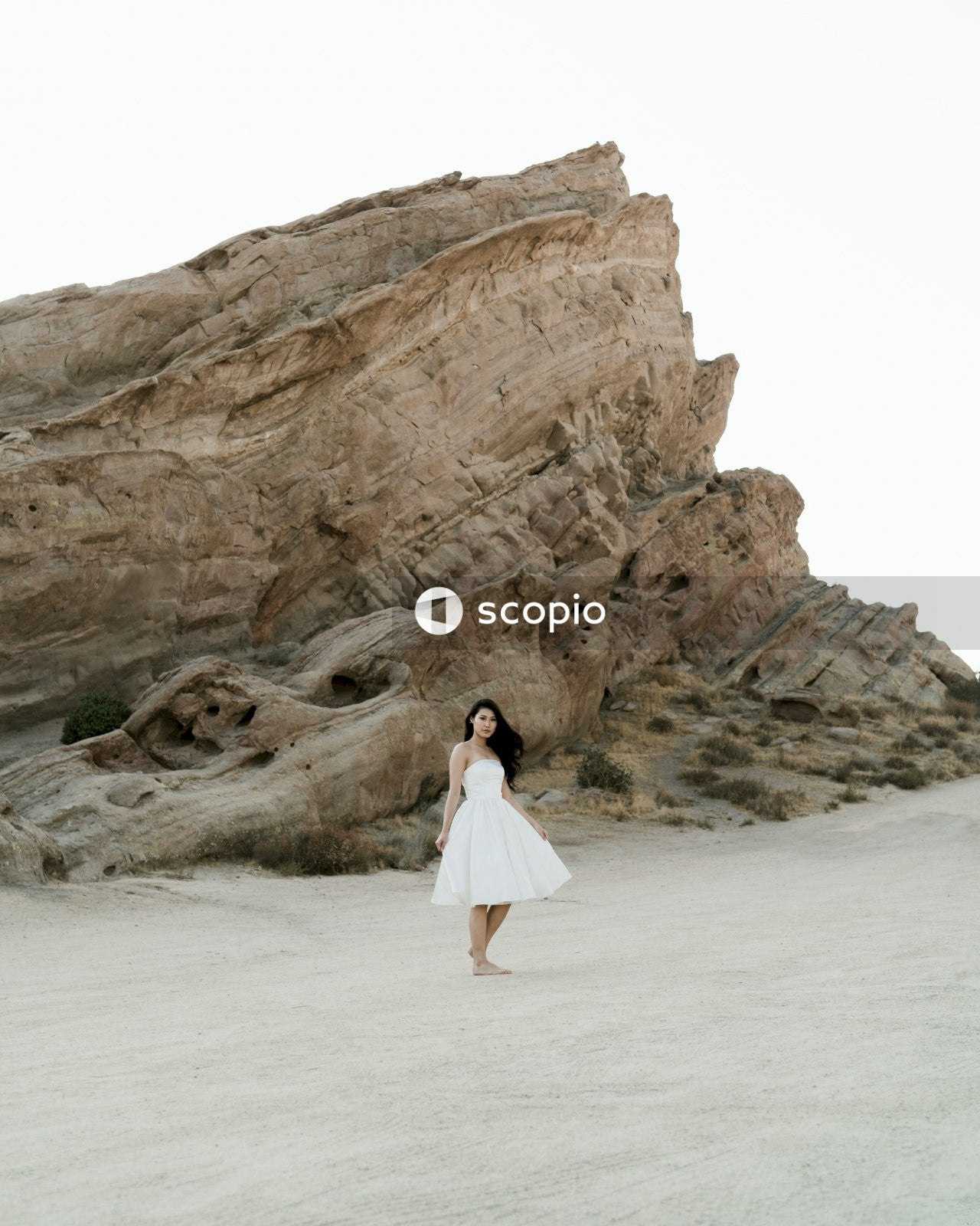 Woman in white dress standing on white sand near brown rock formation