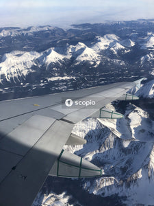 Gray airplane flying near snow covered mountain