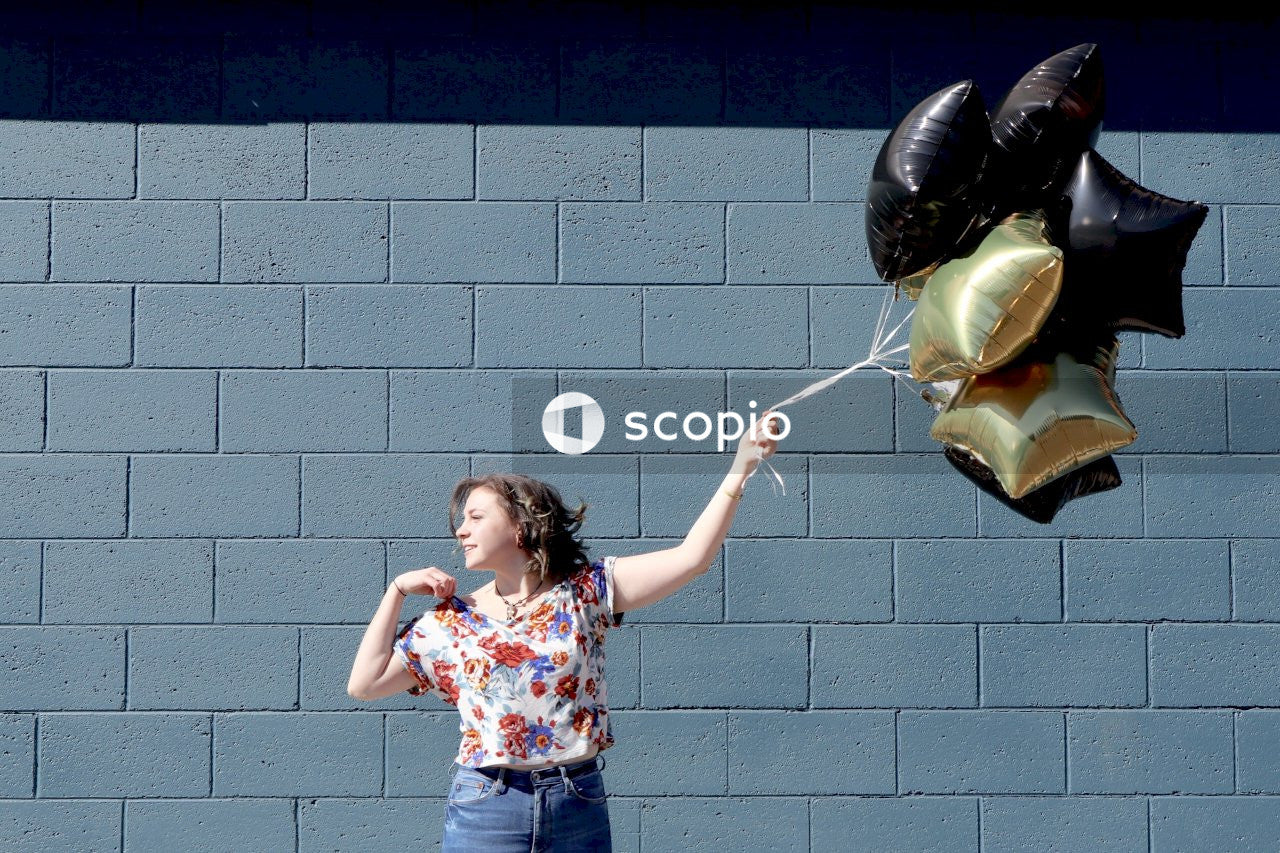 Girl holding black and gold balloons outdoor