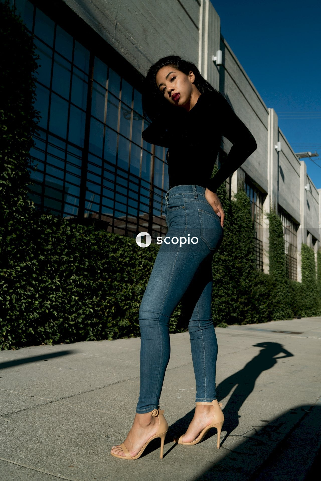 Woman in black long sleeve shirt and blue denim jeans standing on gray concrete floor