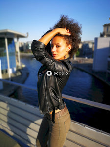 Woman in black leather jacket and brown pants standing near body of water
