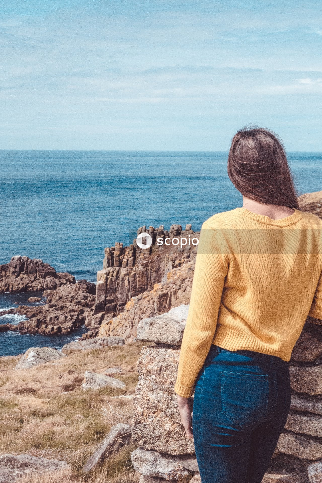 Woman in yellow sweater and blue denim jeans standing on rock formation near sea
