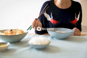 Woman holding chopsticks sitting at table with food